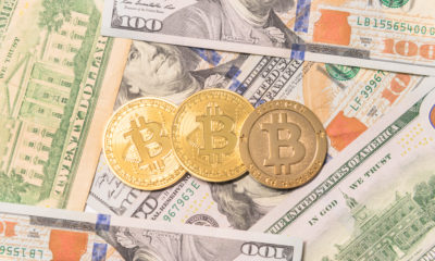 Close-up golden Bitcoin (Cryptocurrency) on US dollars.